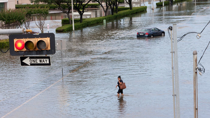A woman walks in the flood waters in southwest Houston, Texas May 26, 2015. (Reuters/Daniel Kramer)