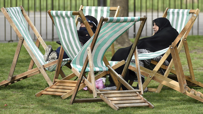 Women relax on deckchairs during hazy sunshine in Hyde Park in central London (Reuters / Toby Melville)