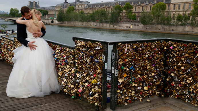 """A recently-married couple from Poland, Dominika and Bartek Mieczkowski, embrace near grills covered with """"love locks"""" on a walkway which leads to the Pont de Arts over the River Seine in Paris, France (Reuters / John Schults)"""