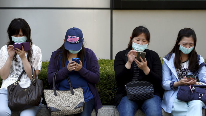 Chinese tourists wearing masks to prevent contracting Middle East Respiratory Syndrome (MERS) use their mobile phones in central Seoul, South Korea June 3, 2015. (Reuters/Kim Hong-Ji)