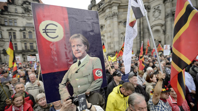 Supporters of the German right-wing movement PEGIDA (Patriotic Europeans Against the Islamisation of the Occident) hold up a poster showing German Chancellor Angela Merkel in a uniform with an Euro-logo-armband as they attend a PEGIDA rally on June 1, 2015 in Dresden, eastern Germany. (AFP Photo/Jens Schlueter)
