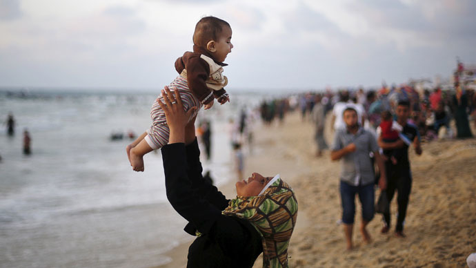 A Palestinian girl lifts her brother as she plays with him on a beach on the Mediterranean Sea, off the coast of Gaza City (Reuters/Mohammed Salem)