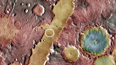 A possible Martian site (white circle) is the Nili Fossae trough. The blue-tinted Hargraves crater at the right (blue indicates a low topography) is known to contain impact glass. (NASA/JPL-Caltech/Arizona State University)
