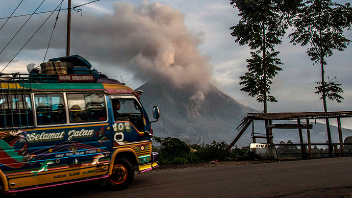 A public bus drives past Mount Sinabung volcano (background) as it spews volcanic ashes into the air in Karo district in North Sumatra province on June 10, 2015 (AFP Photo / Sutanta Aditya)