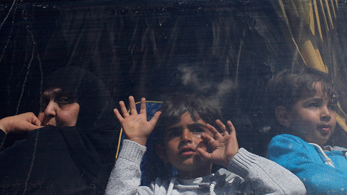 Palestinians look out a bus window (Reuters / Ibraheem Abu Mustafa)