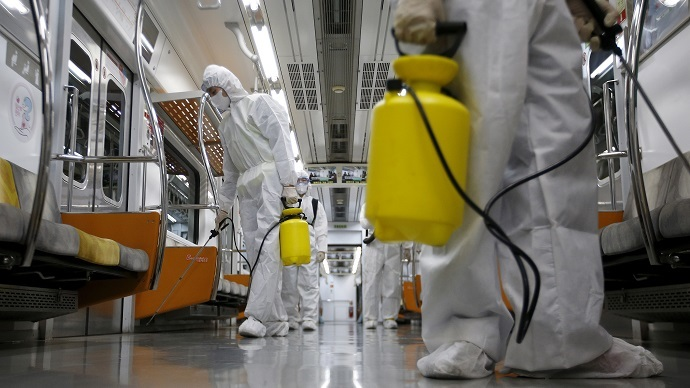 Workers in full protective gear disinfect the interior of a subway train at a Seoul Metro's railway vehicle base in Goyang, South Korea. (Reuters / Kim Hong-Ji)