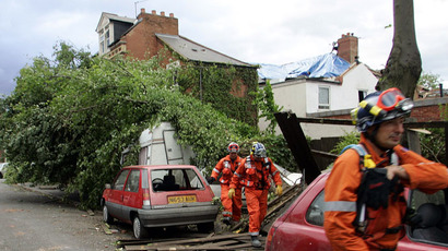 Workers walk past a caravan crushed by a fallen tree after a tornado struck the Moseley area of Birmingham, central England, July 28, 2005. (Reuters/Darren Staples)