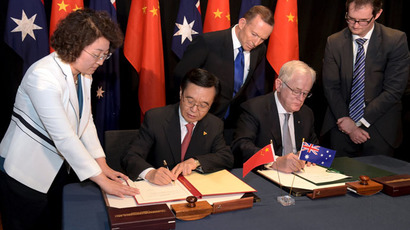 Australian Prime Minister Tony Abbott (C) watches as China's Minister of Commerce Gao Hucheng (2nd L) and Australian Minister for Trade Andrew Robb (2nd R) sign a trade agreement during an official signing ceremony in Canberra June 17, 2015. (Reuters/Lukas Coch)