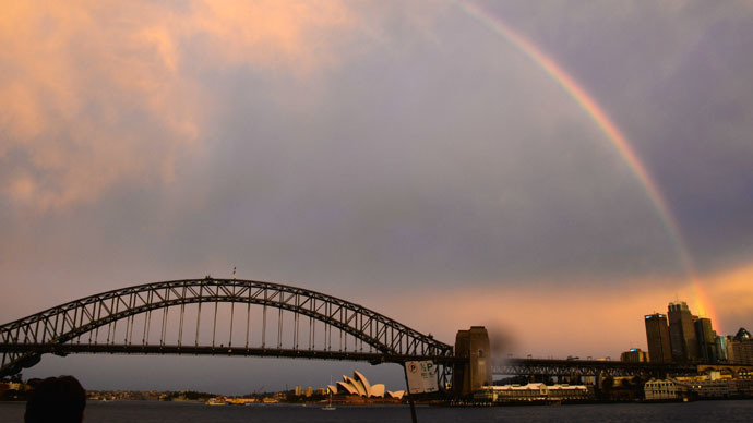 A rainbow is seen beyond the landmark Harbour Bridge and Opera House during sunset on a rainy day in Sydney on June 17, 2015. (AFP Photo/Saeed Khan)