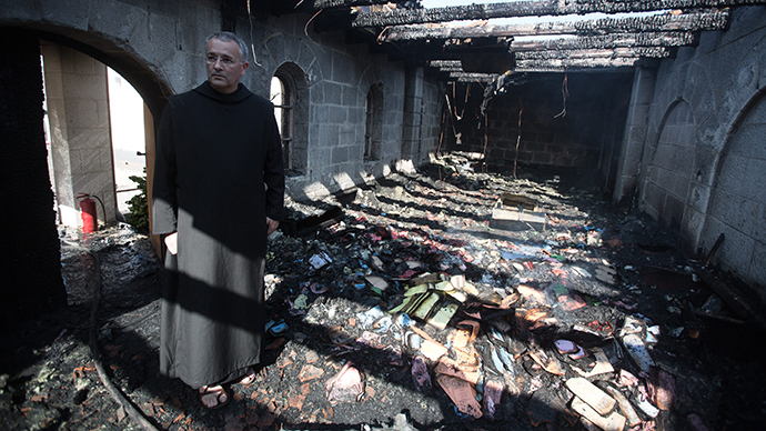 A priest inspects the damage at a room located on the complex of the Church of the Multiplication at Tabgha, on the shores on the Sea of Galilee in northern Israel, on June 18, 2015, in the aftermath of a suspected arson attack (AFP Photo / Menahem Kahana)