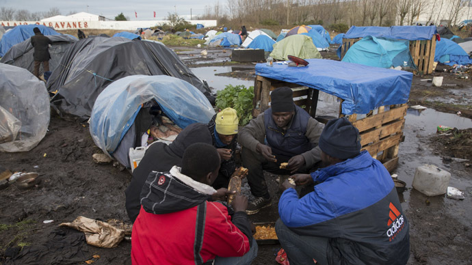Sudanese migrants eat a meal near tents and makeshift shelters at a camp in Calais. (Reuters / Philippe Wojazer)