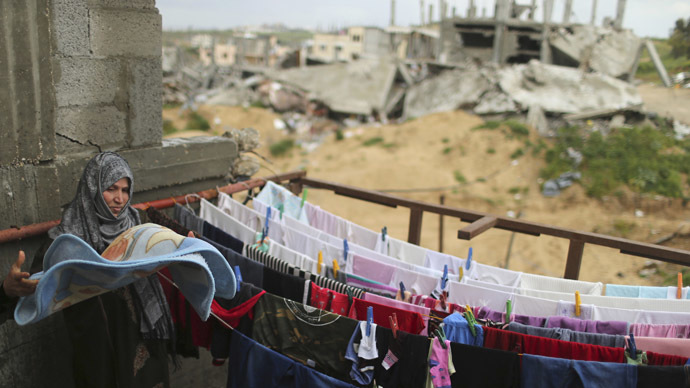 A Palestinian woman hangs laundry at her damaged house as ruins of houses that witnesses said were destroyed by Israeli shelling during a 50-day war last summer are seen, on a rainy day east of Gaza City. (Reuters / Suhaib Salem)