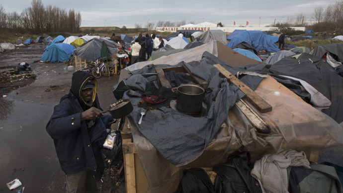 A Sudanese migrant prepares a meal outside a makeshift shelter at a tent camp in Calais. (Reuters / Philippe Wojazer)