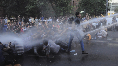 Protesters are hit by jets of water released from a riot police vehicle during a rally against a recent decision to to increase the tariff on electricity, in Yerevan, Armenia, June 23, 2015 (Reuters / Narek Aleksanyan)