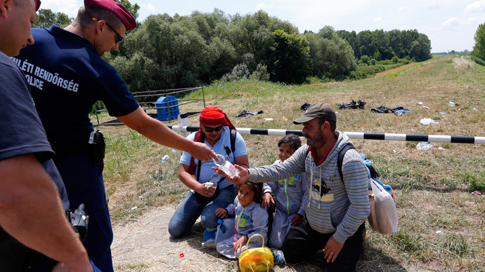 Hungarian police give water to migrants from Syria who crossed the border from Serbia to Hungary, walking on the dam near the Tisza river near the city of Szeged, Hungary, on June 29, 2015. (Reuters / Laszlo Balogh)