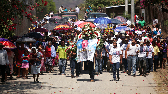 A man carries a wreath and a banner as relatives and friends of Antonio Zambrano-Montes carry his coffin toward the cemetery in Pomaro, in the Mexican state of Michoacan March 7, 2015 (Reuters / Alan Ortega)
