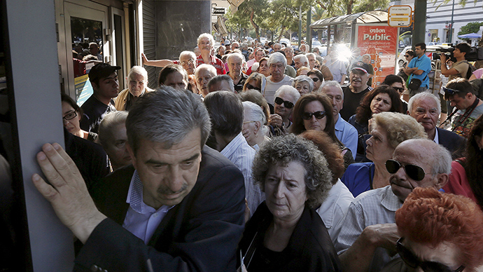 A manager tries to close the door of a bank as hundreds of pensioners line up outside a National Bank in Athens, Greece, July 1, 2015 (Reuters / Yannis Behrakis)