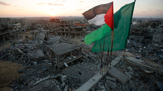 A Palestinian flag and a Hamas flag (R) flutter atop the wreckage of a house, which witnesses said was destroyed during the seven-week Israeli offensive, in the east of Gaza City September 3, 2014 (Reuters / Suhaib Salem)