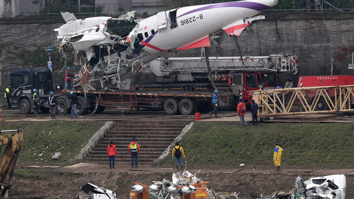 Emergency teams remove pieces of wreckage at the site of the crashed TransAsia Airways plane Flight GE235 in New Taipei City February 5, 2015.(Reuters / Pichi Chuang)