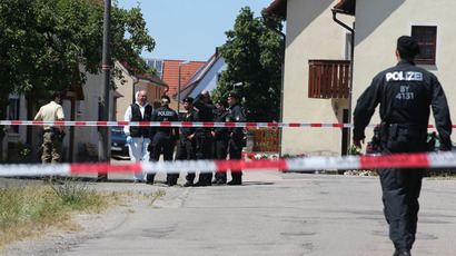 Policemen stand at a crime scene in Tiefenthal-Leutershausen near Ansbach, southern Germany, after a gunman in a car killed a woman and a cyclist in drive-by shootings on July 10, 2015. (AFP Photo/DPA)