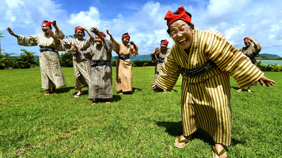 In this picture taken on June 22, 2015, an elderly women troupe of singers and dancers from Kohama Island in Okinawa wearing traditional local costumes perform at a herb garden on Kohama Island, Okinawa Prefecture. (AFP Photo/Toru Yamanaka)