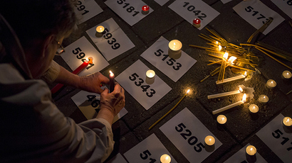A woman lights candles between papers with numbers symbolizing the victims of the 1995 Srebrenica massacre, in downtown Belgrade, Serbia July 10, 2015 (Reuters / Marko Djurica)