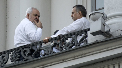 Iranian Foreign Minister Mohammad Javad Zarif (L) and Hossein Fereydoun, the brother of the Iranian president, talk during abreak onto a balcony of the Palais Coburg Hotel, where the Iran nuclear talks meetings are being held in Vienna on July 11, 2015. (AFP Photo/Joe Klamar)