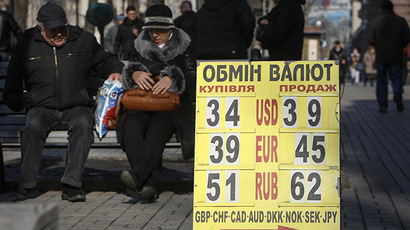 People sit next to a board showing  exchange rates in central Kiev. (Reuters / Valentyn Ogirenko)