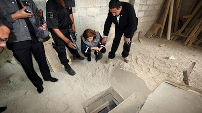 Mexican law enforcers look into the entrance of a tunnel used by drug lord Joaquin 'El Chapo' Guzman to escape from prison. (Reuters / PGR - Attorney General's Office / Handout via Reuters)