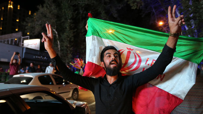 An Iranian man flashes the victory sign as an other holds the Iranian national flag during celebration in northern Tehran on July 14, 2015,after Iran's nuclear negotiating team struck a deal with world powers in Vienna. (AFP Photo/Atta Kenare)