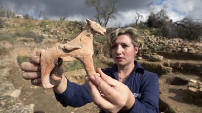 Israel Antiquities Authority archeologist Anna Ririkh displays a clay figurine (AFP Photo / Menahem Kahana)
