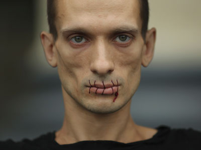 "Artist Pyotr Pavlensky, a supporter of jailed members of female punk band ""Pussy Riot"", looks on with his mouth sewed up as he protests outside the Kazan Cathedral in St. Petersburg.(REUTERS / Trend Photo Agency / Handout)"