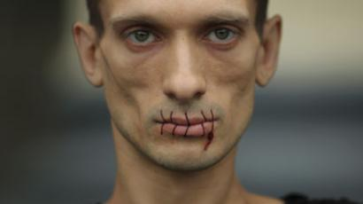 """Artist Pyotr Pavlensky, a supporter of jailed members of female punk band """"Pussy Riot"""", looks on with his mouth sewed up as he protests outside the Kazan Cathedral in St. Petersburg.(REUTERS / Trend Photo Agency / Handout)"""