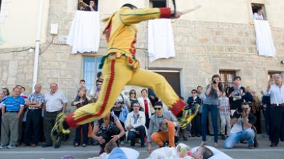 A man dressed in a red and yellow costume representing the devil, known as El Colacho, jumps over babies placed on a mattress during traditional Corpus Christi celebrations in Castrillo de Murcia, near Burgos, northern Spain June 10, 2012 (Reuters/Ricardo Ordonez)