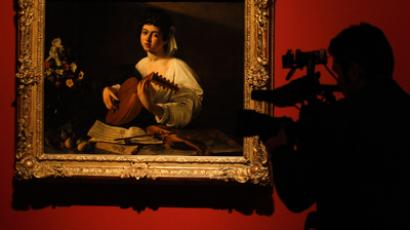 """A cameraman films the """"Lute Player"""", a painting by Caravaggio, during the media preview of """"The Hermitage in the Prado"""" exhibition in Madrid (Reuters / Andrea Comas)"""
