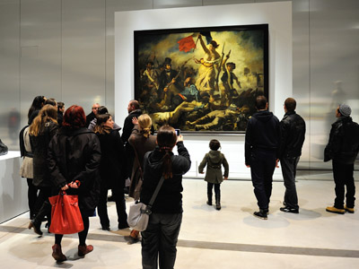 """A file picture taken on December 3, 2012 at the Louvre-Lens Museum in the French northern city of Lens, shows a visitor passing by the Eugene Delacroix masterpiece """"La Liberté guidant le Peuple"""" (Liberty leading the people). (AFP Photo/Philippe Huguen)"""