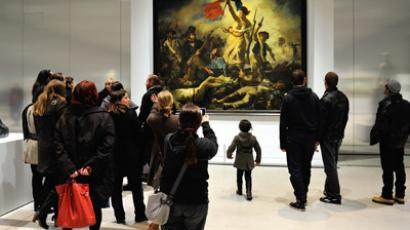 "A file picture taken on December 3, 2012 at the Louvre-Lens Museum in the French northern city of Lens, shows a visitor passing by the Eugene Delacroix masterpiece ""La Liberté guidant le Peuple"" (Liberty leading the people). (AFP Photo/Philippe Huguen)"