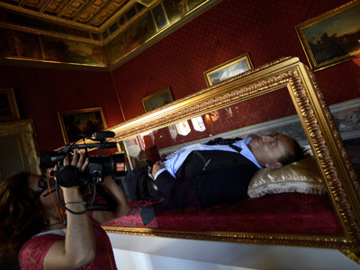 """A woman films on May 29, 2012 the work of Italian artists Antonio Garullo and Mario Ottocento, called """"The Dream of Italians,"""" showing a wax figurine former Italian Prime Minister Silvio Berlusconi inside a shrine, at the Ferrajoli Palace in the center of Rome. (AFP Photo/Filippo Monteforte)"""