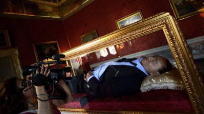 "A woman films on May 29, 2012 the work of Italian artists Antonio Garullo and Mario Ottocento, called ""The Dream of Italians,"" showing a wax figurine former Italian Prime Minister Silvio Berlusconi inside a shrine, at the Ferrajoli Palace in the center of Rome. (AFP Photo/Filippo Monteforte)"
