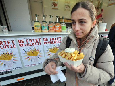 A woman eats French fries (fried chips) (AFP Photo / Georges Gobet)