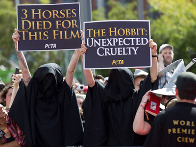 "Animal rights campaigners from PETA hold up placards in protest next the red carpet during the world premiere of ""The Hobbit"" movie in Courtenay Place in Wellington on November 28, 2012. (AFP Photo / Marty Melville)"