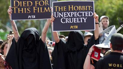 """Animal rights campaigners from PETA hold up placards in protest next the red carpet during the world premiere of """"The Hobbit"""" movie in Courtenay Place in Wellington on November 28, 2012. (AFP Photo / Marty Melville)"""