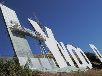Workers use window-cleaner style platforms as they strip down the 50-foot (15-meter) tall letters, power washing the corrugated iron and apply nearly 400 gallons of fresh paint while restoring the Hollywood sign on October 26,2012 in Hollywood, California (AFP Photo / Joe Klamar)