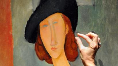 A member of staff discusses a work entitled ''Jeanne Hebuterne (au chapeau)' by Italian artist Amedeo Modigliani at Christies auction house in central London on February 1, 2013 (AFP Photo / Carl Court)