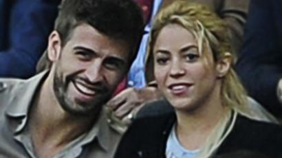Barcelona's defender Gerard Pique sits with Colombia singer  Shakira. (AFP Photo / Josep Lago)
