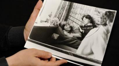 A previously unseen press photo of a teenaged Princess Diana is held by Bobby Livingston of RR Auctions on January 16, 2013. The black-and-white image from the 1980s shows Diana smiling at the camera as she lies in the lap of an unidentified young man reading a book. (AFP Photo)