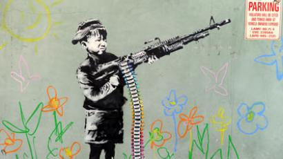 A graffiti attributed to secretive British artist Banksy depicting a child wielding a machine gun, in black and white surrounded by colored flowers, is spotted in Westwood, California.(AFP Photo / Gabriel Bouys)