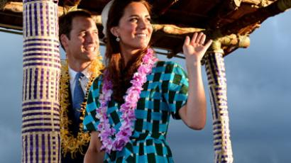 Britain's Prince William (L) and his wife Catherine, the Duchess of Cambridge, wave to the local Solomon Islanders as they leave the airport aboard a truck decorated as canoe in Honiara.(AFP Photo / William West)