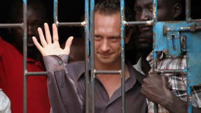 This file picture shows British theatre producer David Cecil waving from a court cell at the Makindye Court on September 13, 2012 in Kampala.(AFP Photo / Isaac Kasamani)