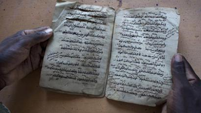 Aboubakar Yaro, head of conservation at the Djenne Library of Manuscipts, holds an Islamic manuscript from the 15th century in Djenne. (Reuters / Joe Penney)